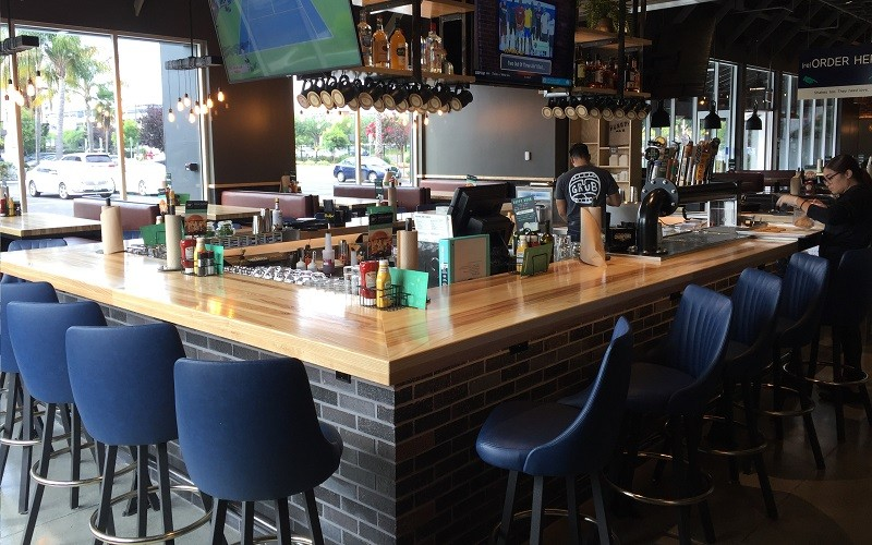 Fully Upholstered Custom Channel Back Swivel Bucket Barstools adorn the bar area